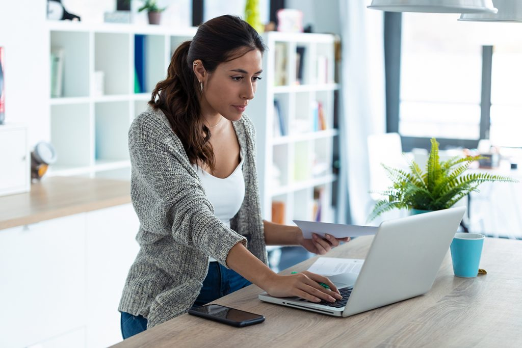young woman working with laptop and documents in the kitchen at home.